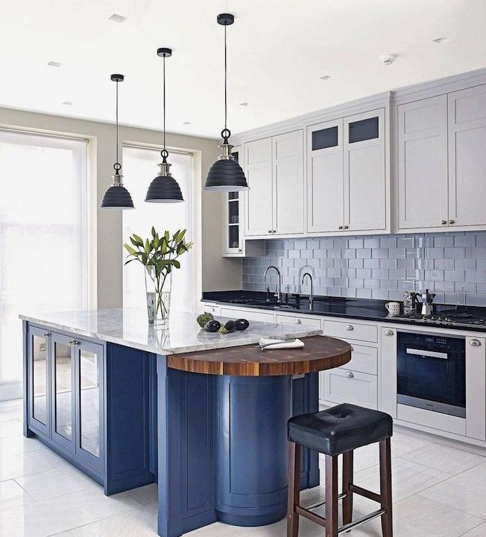 ilot central bleu dans une cuisine blanche et grise avec meubles cuisine blancs, carrelage credence gris
