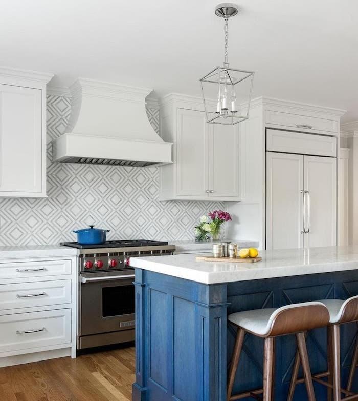 ilot central bleu avec plan de travail blanc, meuble cuisine blanc, suspension bougies, parquet clair