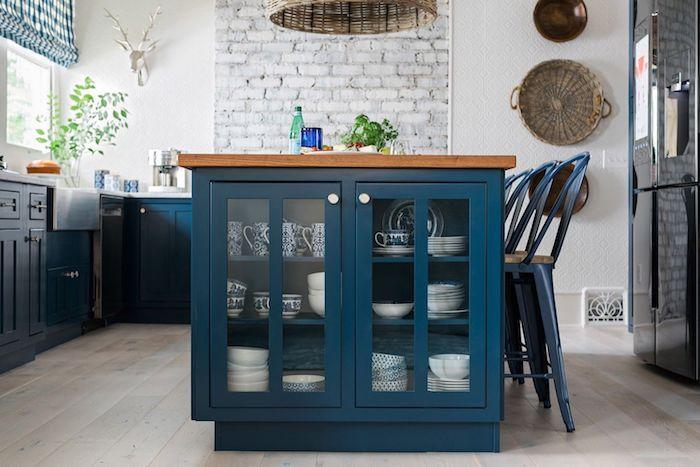 ilot central et meuble bas de couleur bleu dans une cuisine avec pan d e muir de briques, parquet clair, murs blancs, frigo noir