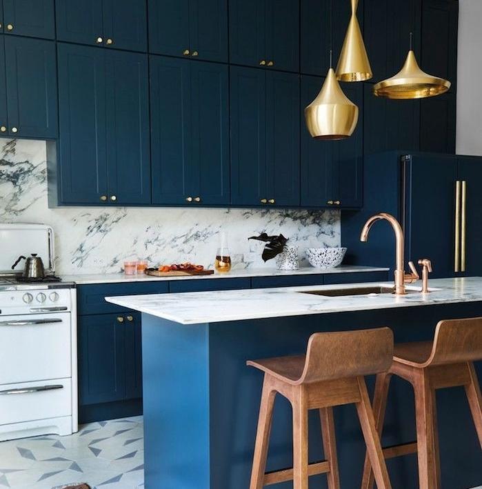 ilot central couleur bleu foncé et meuble haut et bas cuisine bleu nuit, credence de marbre et carrelage gris et blanc