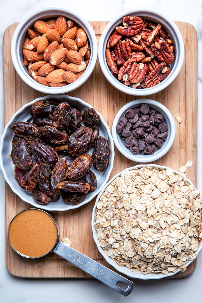 ingredients necessaires pour faire des barres protéinées maison, dattes, amandes et noix de pécan, pepites de chocolat, flocons d avoine