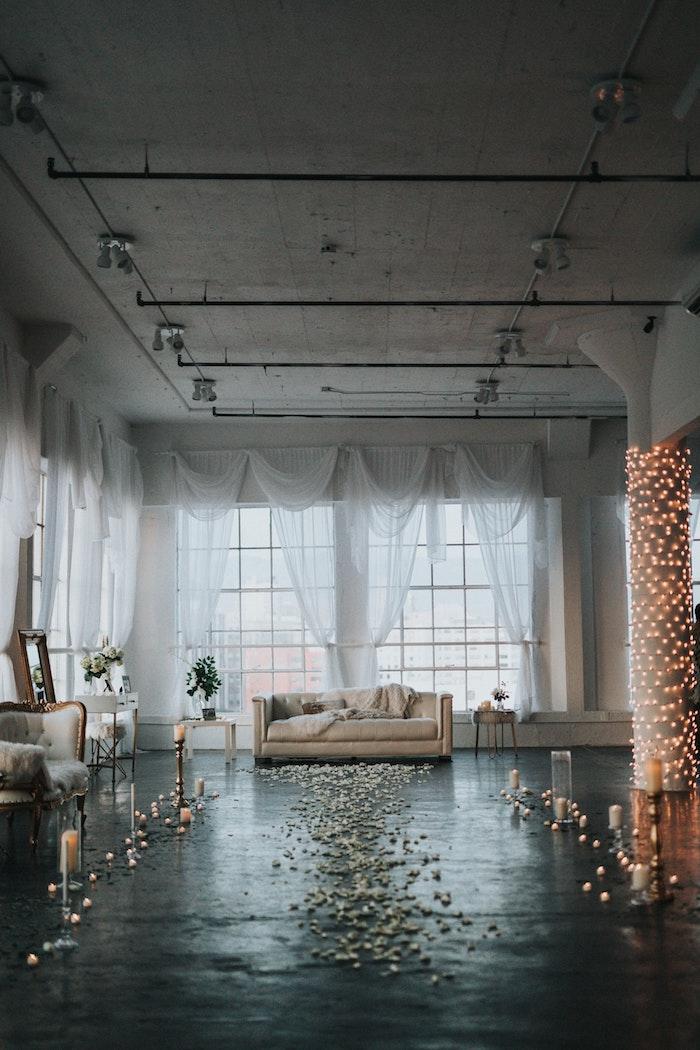 Salle de réception mariage, canapé beige, guirlandes lumineuses, bougies et pétales sur le sol, photo magnifique