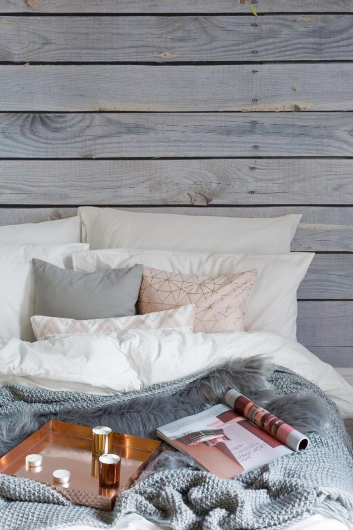 exemple de lit cocooning décoré de coussins et de plaids en couleurs neutres dans une chambre aux murs à effet planches de bois