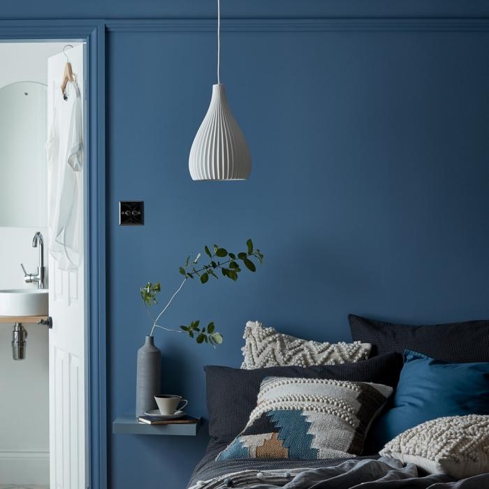 idée de deco chambre parentale aux murs bleu foncé avec un lit cocooning couvert de coussins en nuances de bleu