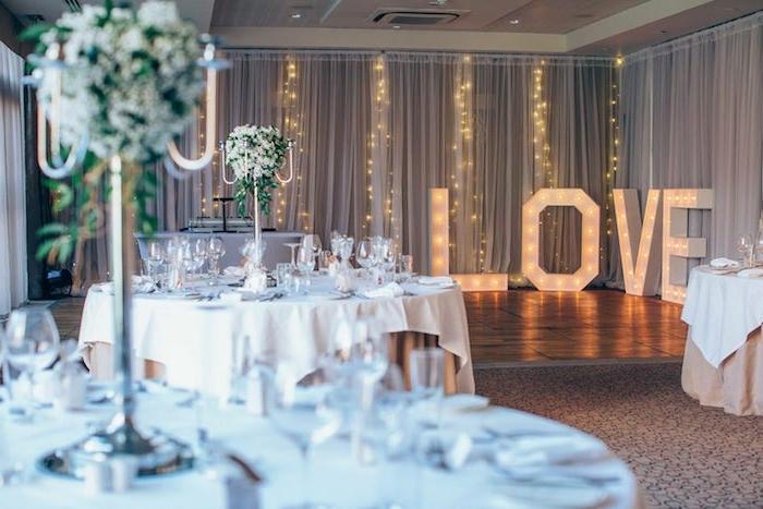 theme de mariage romantique avec decoration de guirlande lumineuse, lettrs lumineuses, bouquets de fleurs blanches sur tables avec nappe blanche et beige