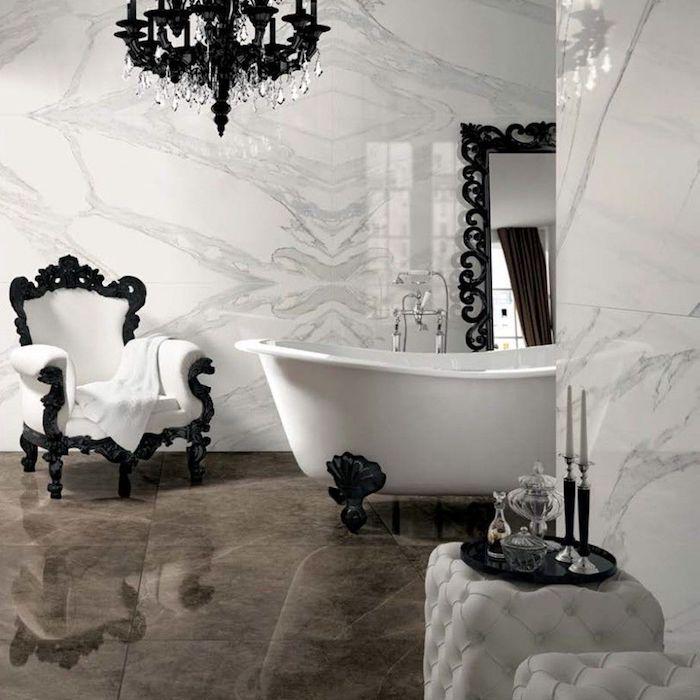 Salle de bains blanc et noir style baroque, lustre noire avec cristaux, fauteuil textile blanc et cadre noir, inspiration salle de bain luxe, amenagement salle de bain blanc marbre