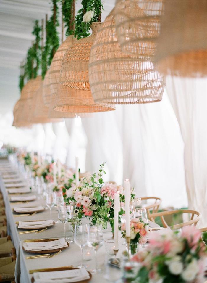 decoration de salle de mariage, suspensions tressées exotiques au dessus d une table décorée de bouquet de fleurs blanches et rose et vaisselle dorée