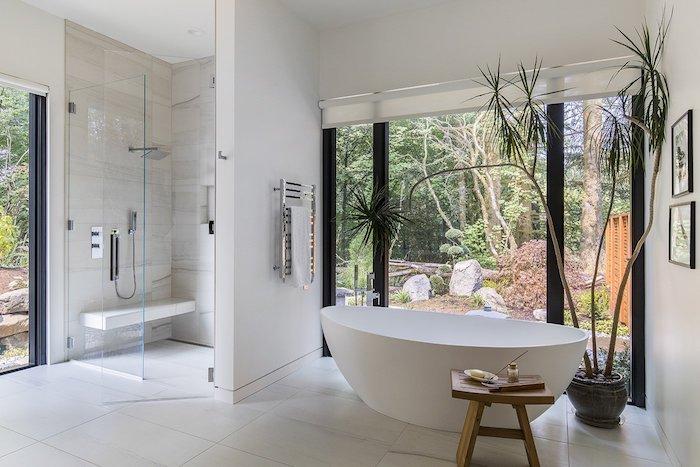 Baignoire ovale dans un espace grand, salle de bain en marbre, design d'intérieur stylé pour une grande pièce vue de jardin