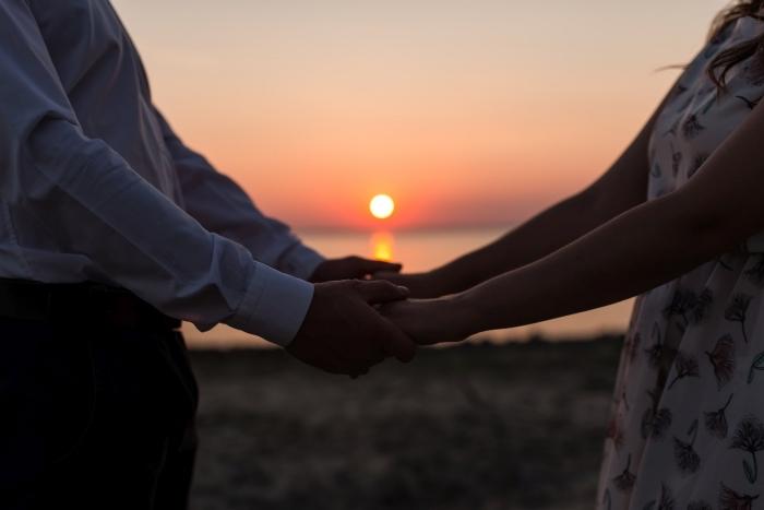 que faire en couple, se balader au bord de la mer au coucher de soleil en couple, femme et homme au coucher de soleil