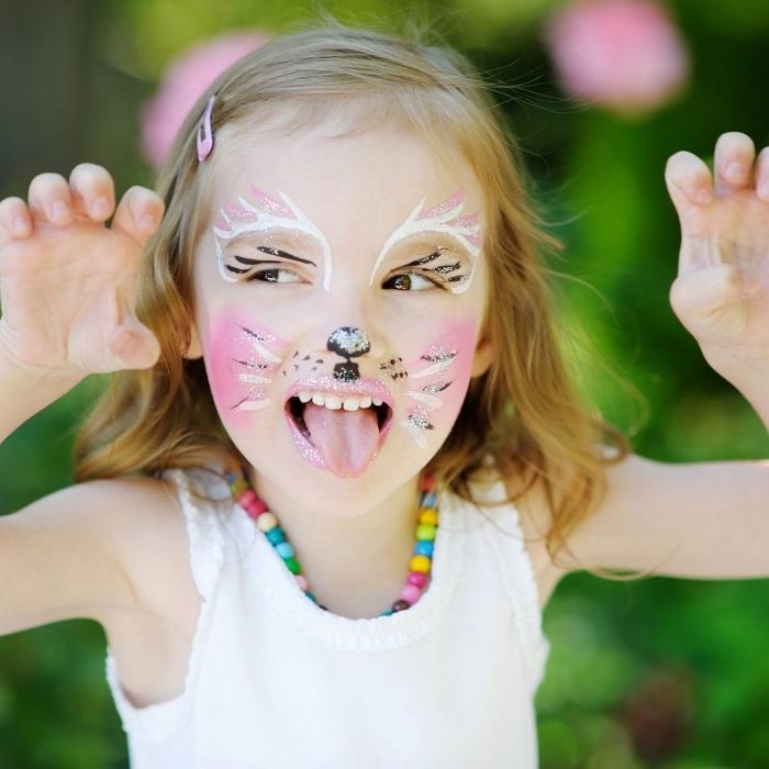 idée de maquillage carnaval facile à réaliser soi-même, fille avec maquillage chat aux joues roses et fourrure en crayon blanc avec moustaches glitter noir