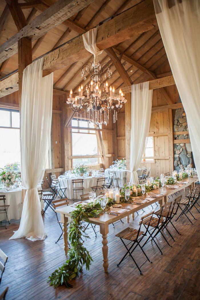 organiser un mariage dans vieilles granges a poutres apparentes lustre vintage, rideaux blancs transparents, table chaises bois et metal, guirlande feuillages et deco bougeoirs