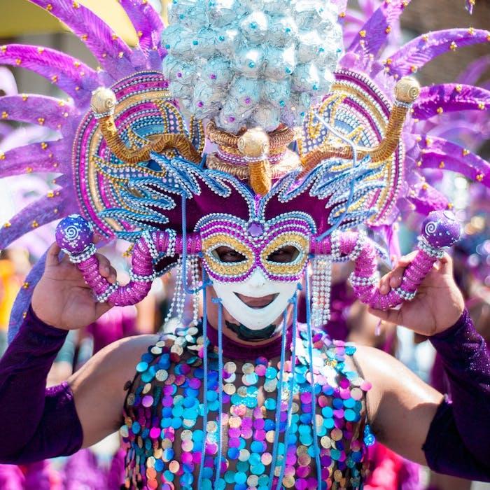 Masque de carnaval, homme habillée en paillettes colorés, carnaval de changement des roles