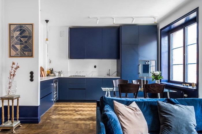 cuisine bleu nuit ouverte sur salon avec canapé bleu foncé, parquet bois, murs blancs et meuble hauts et bas bleu foncé de nuancier pantone
