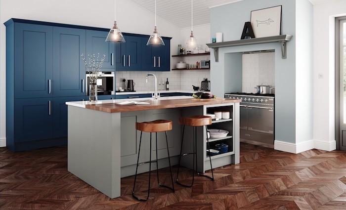 décoration petite cuisine bleu, blanc et bois avec carrelage blanc en crédence, ilot central bois, tabourets de bar bois et noir