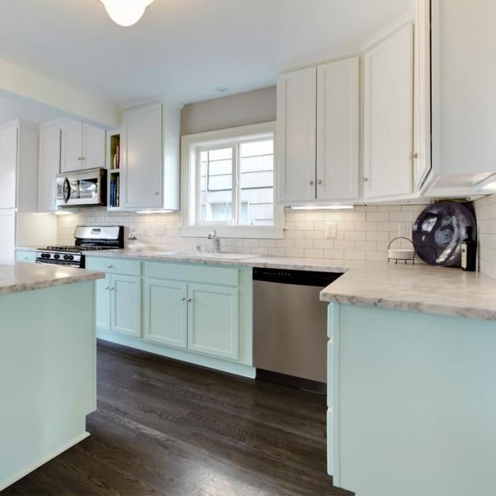 modèles d'armoires de cuisine vert d'eau avec comptoir marbre dans une cuisine blanche au parquet en bois foncé