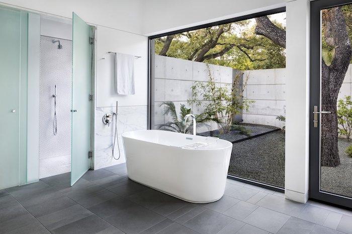 Baignoire ovale dans la salle de bain grand espace qui donne au jardin, choisir le marbre blanc