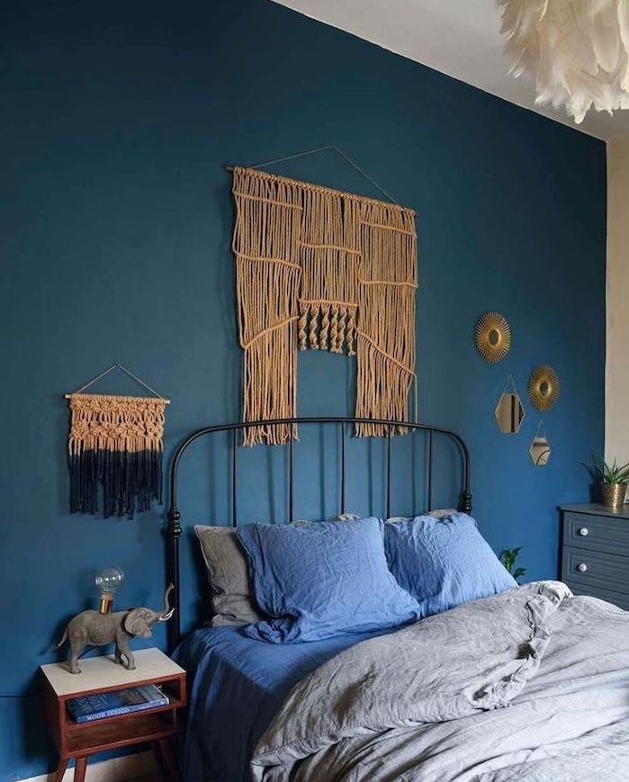 mur de fond de couleur bleu et tete de lit macramé mural dans chambre à coucher gris et bleu, suspension blanche à plumes