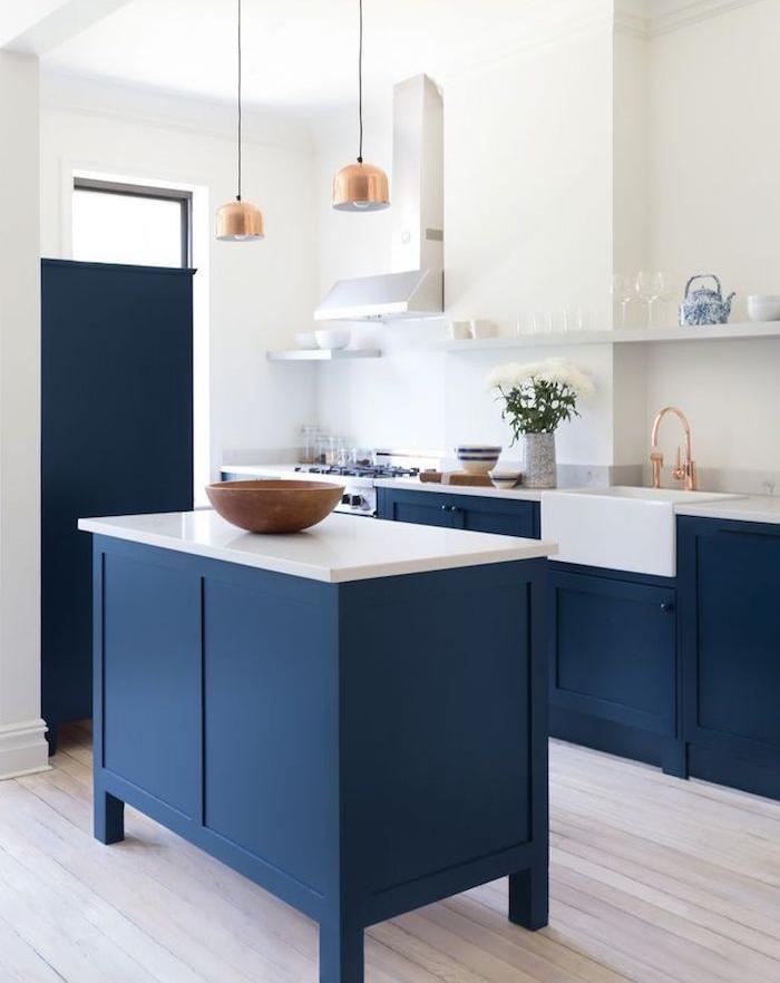 meuble bas et ilot central bleu dans cuisine blanche avec parquet clair et suspensions et robinetterie cuivre
