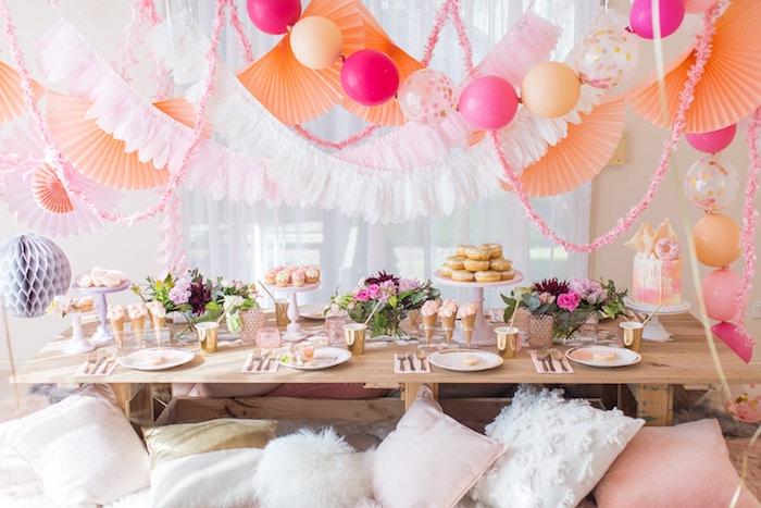 decoration anniversaire boheme chic avec deco ballons, guirlande à éventails, table rustique chic décorée de fleurs, glace beignets et cucpakes, coussins boheme par sol