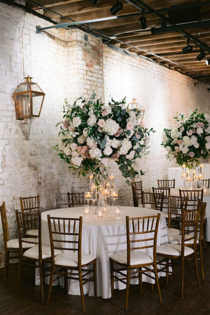 idee deco mariage industriel dans salle de mariage aux murs de briques, déco florale boules de fleurs, bougies dans verres de vin
