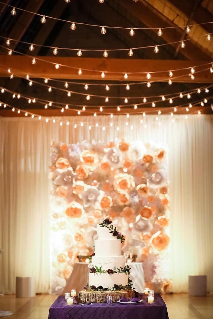 mur de fond mariage décoré de fleurs de papier, guirlandes lumineuses pour decorer le plafond, gateau mariage sur rondin de bois