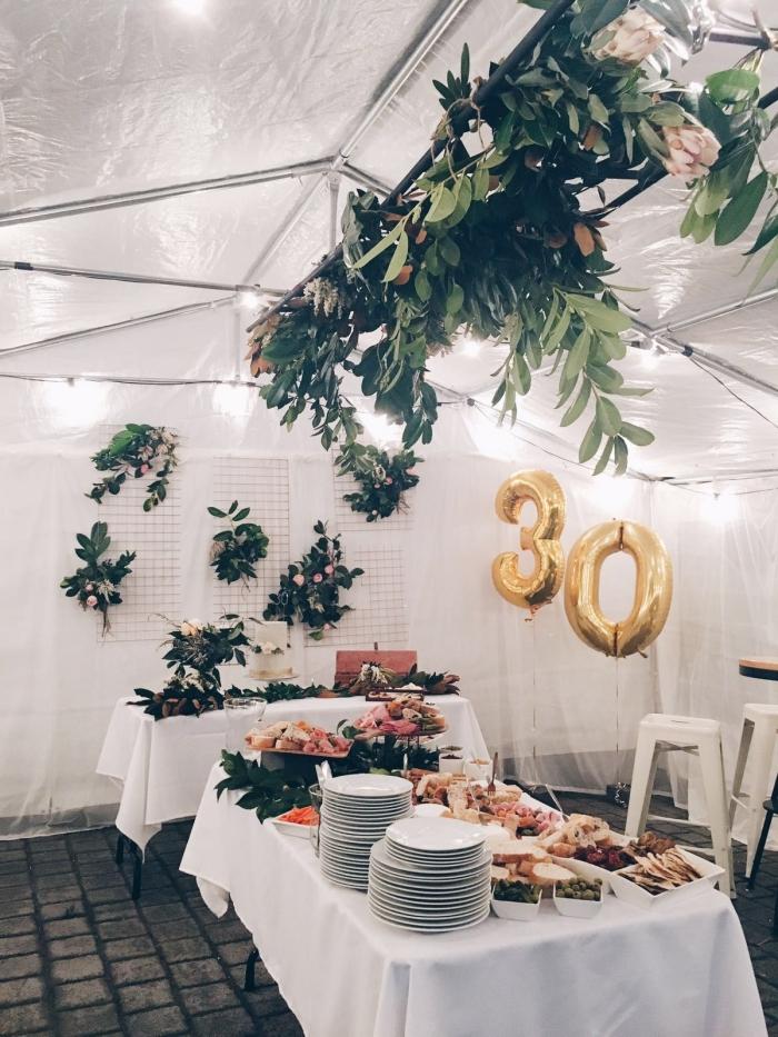 comment organiser un party rustique dans le jardin, idée de décoration table anniversaire adulte avec fleurs fraîches et assiettes blanches
