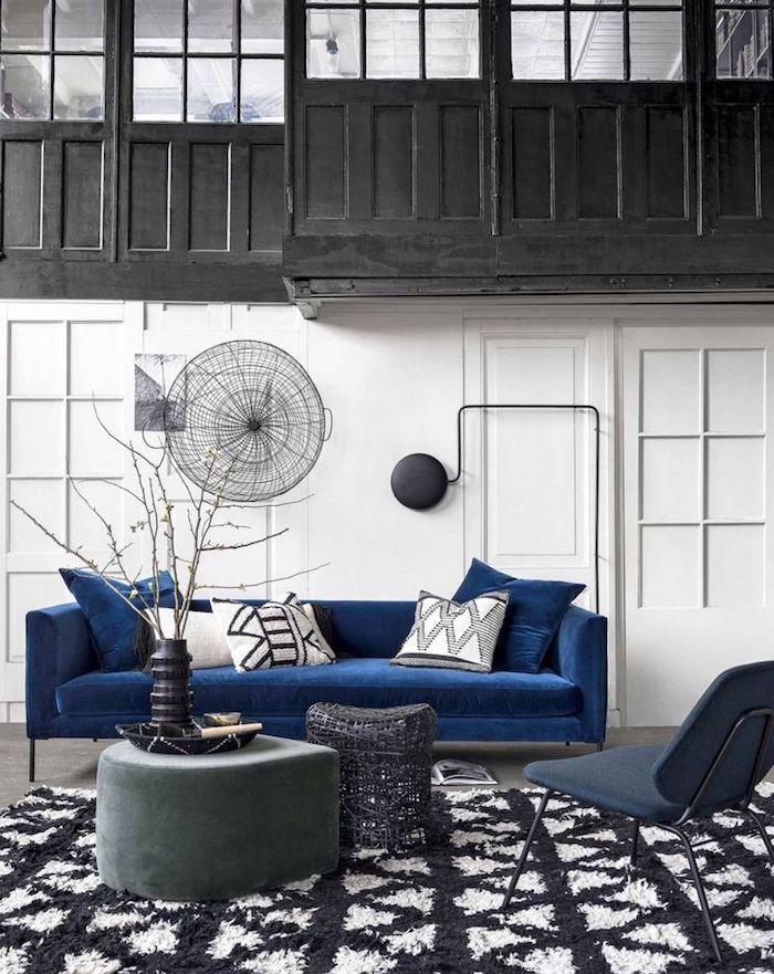 salon noir et blanc avec accent bleu canapé bleu foncé, tapis noir et blanc, murs blancs