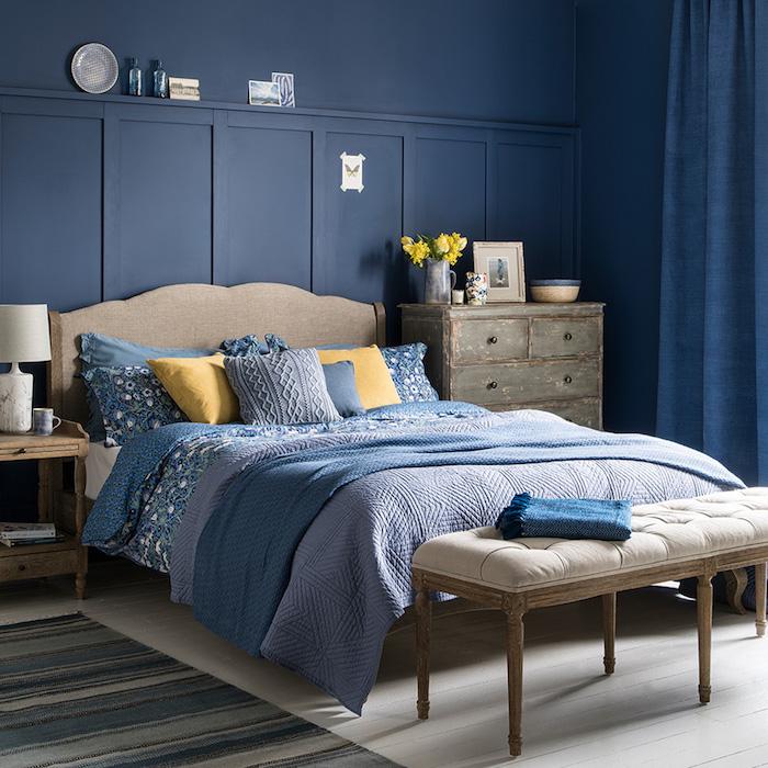idee deco chambre bleue, commode usé, linge de lit bleu et coussina jaunes, amenagement chambre vintage en couleur tendance 2020 peinture