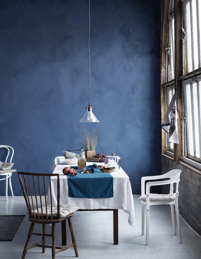 salle à manger contemporaine en bleu foncé, sol et nappe blanche sur table de bois, grandes fenetres, suspension basse