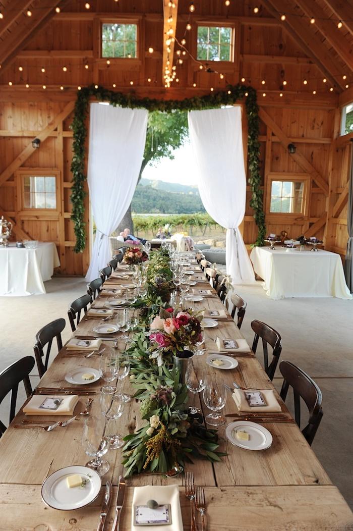 mariage style champetre chic dans vieilles granges de bois, idee deco mariage campagne, guirlande vegetale sur table bois brut