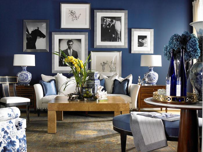 canapé blanc et table basse bois dans un salon aux murs bleus de cadres photos et dessins noir et blanc, accents bleus