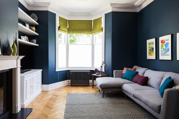 amenagement salon en longueur aux murs bleus et canapé gris décoré de coussins colorés, cheminée blanche, radiateur gris