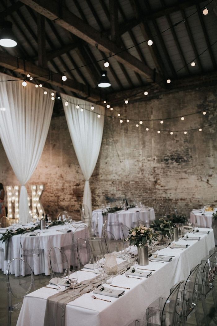 deco industrielle mariage vieille usine, décorée à rideaux transparents blancs, tables décorées de nappes blanches et chemin de table tissu gris, vase métalliques, guirlande lumineuse interieur deco