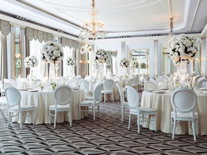 nappes, chaises et fleurs blanches pour décorer une salle de mariage élégante avec tapis marron, noir et gris