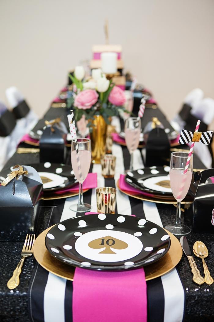 décoration de table party entre fille en couleur glamour or avec accents roses et blanc noir, pliage de serviette rose fuchsia sous assiette