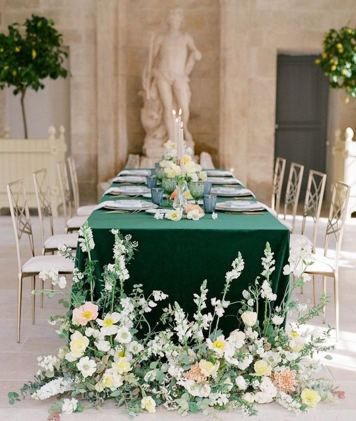 verres de couleur bleue et assiettes blanches sur nappe verte, table entourée de chaises argent et blanc, pieds de table fleuris, statuettes romaines