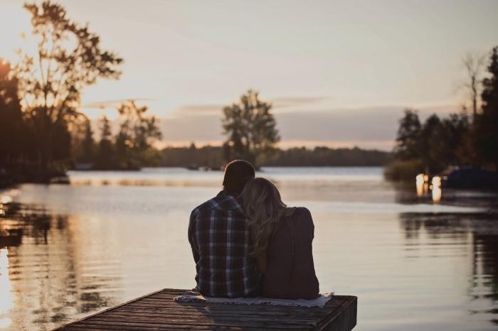 photo de couple amoureux qui observe le coucher de soleil romantique au bord d'un lac, idée rendez-vous dans un endroit romantique