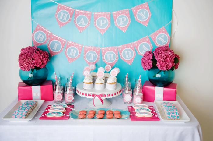candy bar thème spa en rose et bleu avec des bouquets de fleurs fuchsia, cupcakes, macarons, biscuits décorés
