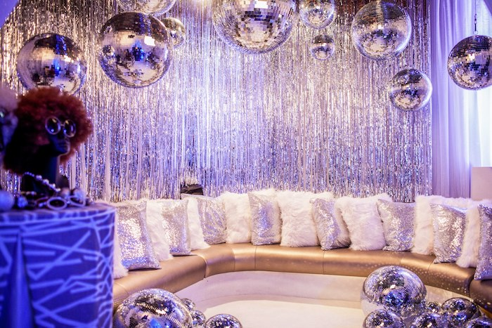 rideau argent et boules disco argent, canapé d angle or décoré de coussins blanc et argent, deco fete anniversaire