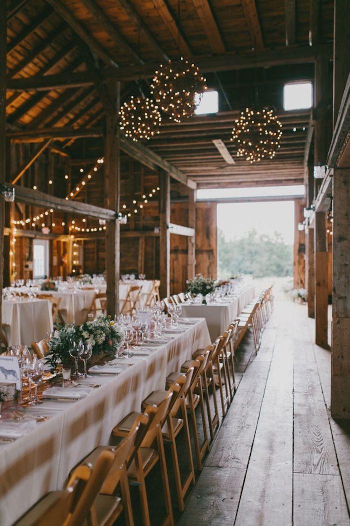 boules de guirlandes lumineuses pour decorer le plafond de vieilles granges rénovées, chaises bois, table avec nappe blanche, deco florale de mariage pour le centre