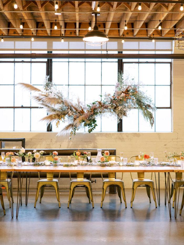 idee decoration industrielle mariage dans usine, table bois chaises industrielles et deco compositions florales style champetre chic