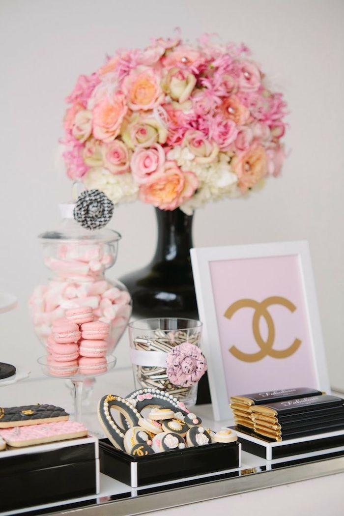 bouquet de fleurs dans un vase noir, dragées, macarons et biscuits noir et rose, chocolats paquet noir et or