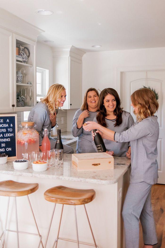 idée anniversaire pyjama party, femmes en pyjamas grises, party cocktails rose et fruits variés, bar avec tabourets bois et metal