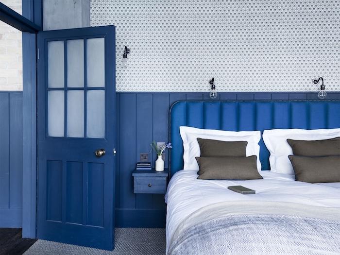 murs et porte bleus, linge de lit gris et blanc sur lit avec tete de lit bleue, tapis gris et blanc, deco vintage couleur peinture salon