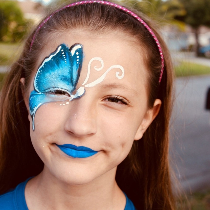dessiner un masque de carnaval avec peinture faciale, modèle de papillon bleu aux ailes ombrées sur le visage d'une fille