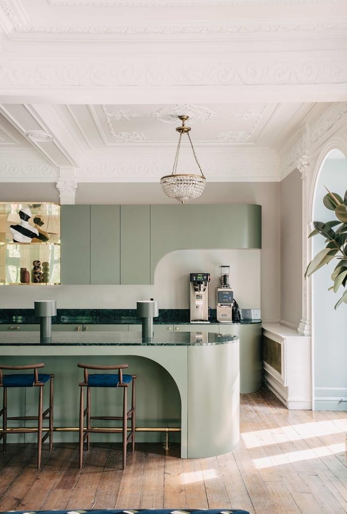 tendance cuisine 2020 de style moderne aux murs gris clair avec meubles en vert olive sans poignées et accents métal