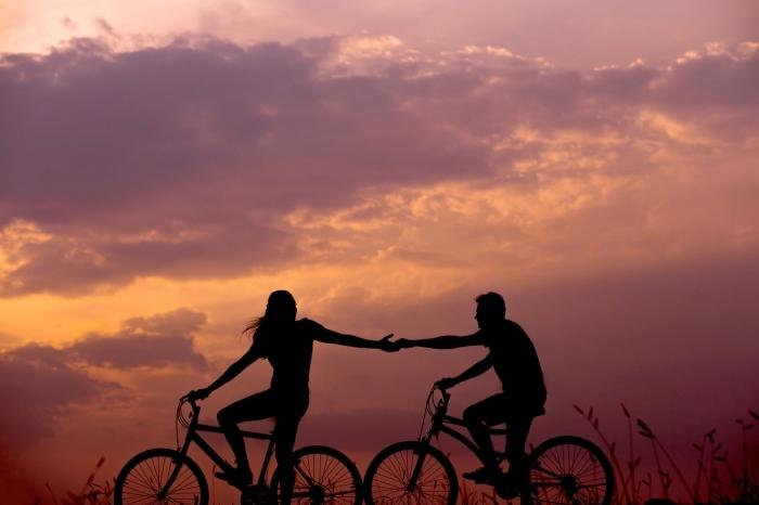 idée amusante d'activité en amoureux, se promener à vélo dans la nature au coucher de soleil en couple amoureux