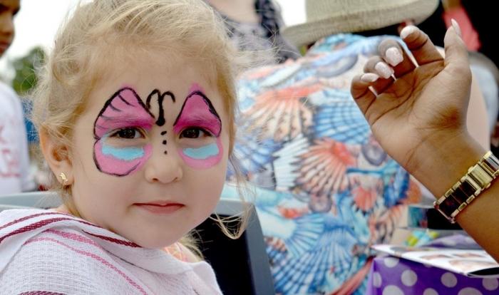 apprendre à dessiner un papillon facile sur visage d'enfant avec des peintures pour visage en couleur rose et bleu