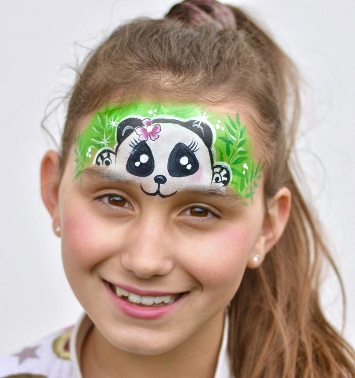 quel maquillage halloween facile pour enfant, dessin sur le front d'une petite fille à design mini panda avec fleur rose sur la tête caché dans l'herbe