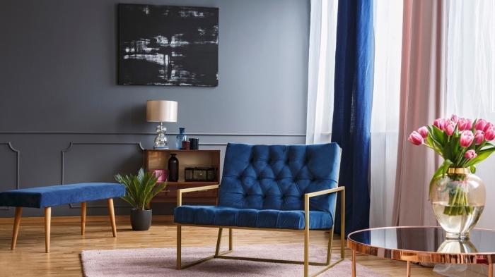 idée de deco salon moderne aux murs gris clair et sol en bois avec meubles en velours bleu marine et accents rose pastel